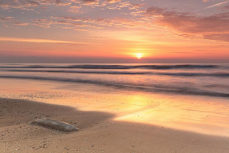 Fotografía hecha justo en el momento en el que el sol aparece. Las nubes lo difuminan, creando una mayor zona iluminada