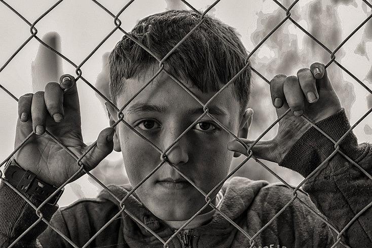 Fotografía de un niño tras una reja